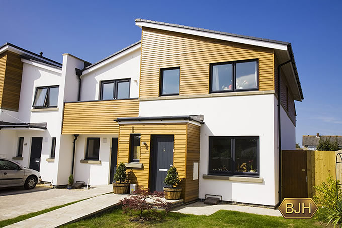 Full view Contemporary modern wood clad home with grey upvc double glazed windows.  Grey doors.  Grey french doors.