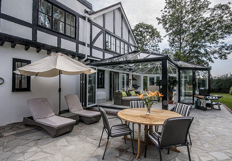 Large P-shaped glass conservatory. White inside & Black outside. Aluminium Bi folding doors.  Glass roof.