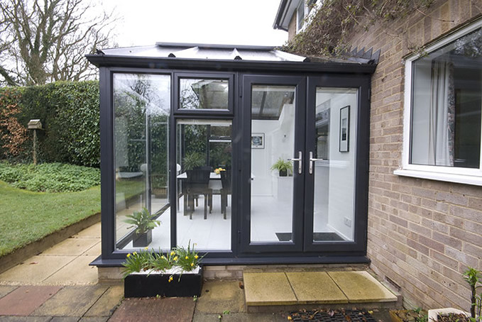 Side view of Black upvc conservatory with glass roof.  Pair of french doors. Modern and contemporary style.