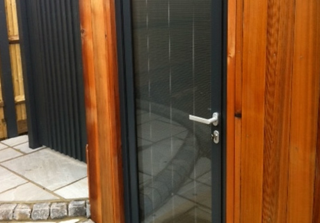 Schuco door in dark grey aluminium featuring internal blinds on a modern studio or contemporary building.