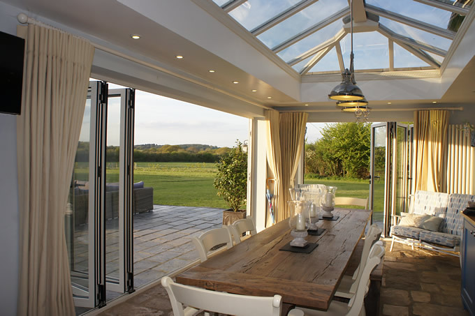 Two sets of Schuco bi-folding doors. One with three panels and the other with five panels.  Cream with black handles. Glass atrium roof with recessed lighting.