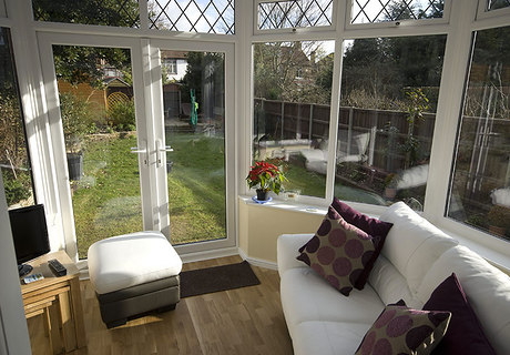 White upvc conservatory with leaded top  opening windows.  Double glazed upvc  french doors.  Polycarbonate roof.