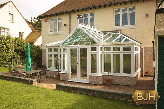 Large white upvc double glazed conservatory with glass roof featuring electric opening vents.  French doors.  Leaded top openers.  Decorative arched glasswork and trims.