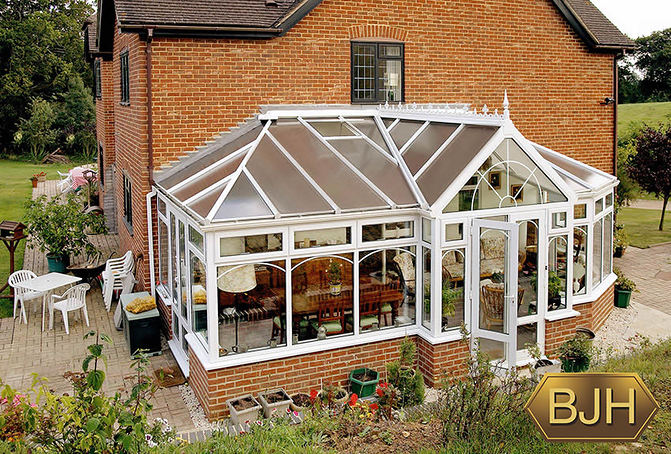 White conservatory with brick.  French doors.  Decorative glass & roof trim.  Polycarbonate  pitched roof. White guttering.