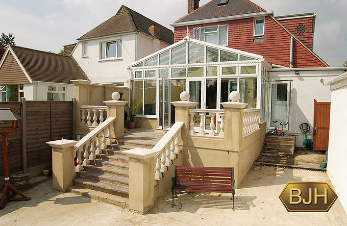 Large white conservatory with multiple glass panels and glass roof.  electric remote control  opening vents. french doors.  side door.