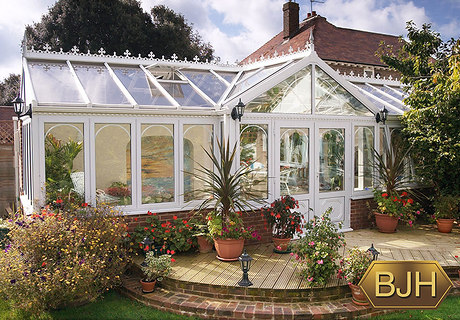 Large white Pvc-u conservatory with glass roof with central french doors. Decorative window bars and roof trims.