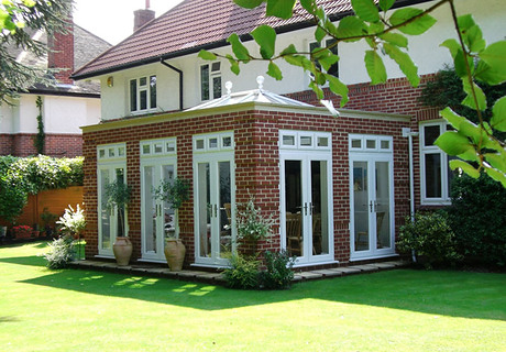 Ornate brick Orangery featuring french doors on three sides & clear glass roof