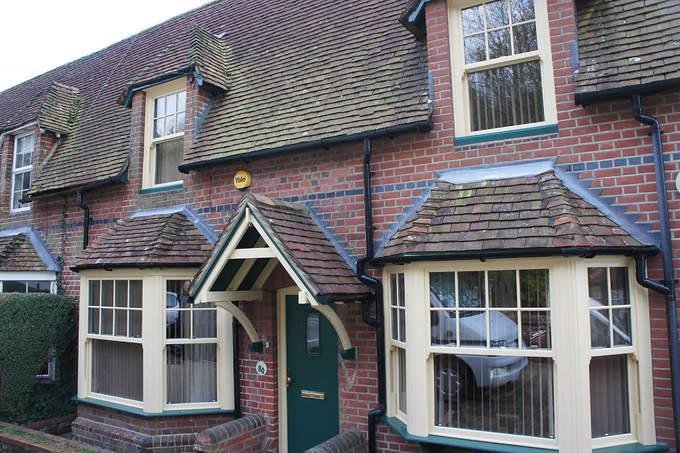 Pvc-u double glazed vertical sliding sash windows and composite door in bespoke colours.  Cream & Green.