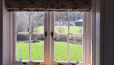 Heritage UPVC Cream sculptured double glazed window with square bars.  Cast iron effect handles and stays.