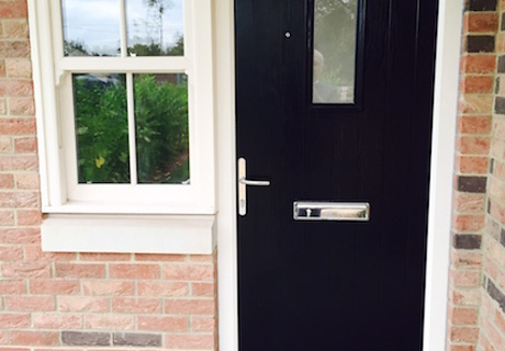 Black Composite Front Door with flanking Cream Pvc-u sliding sash window  - a nod to the traditional style.