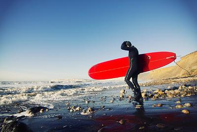 surfer with board on beach, Isle of Wight
